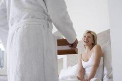 Desayuno de la porción del hombre a la mujer alegre en cama Fotos de archivo libres de regalías