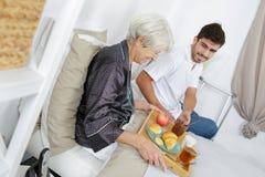 Desayuno de la porción de la enfermera a la mujer mayor en casa imagenes de archivo