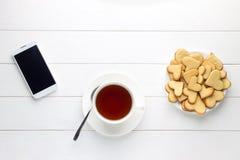 Desayuno de la taza de té y de galletas en forma de corazón y del smartphone en la tabla de madera Imagen de archivo libre de regalías