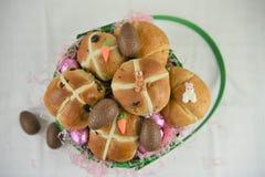 Desayuno de Pascua con los bollos cruzados calientes y los cruasanes frescos con las decoraciones Imagenes de archivo