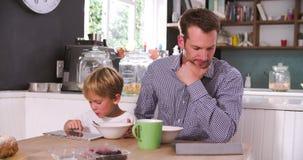 Desayuno de And Son Eating del padre mientras que usa las tabletas de Digitaces metrajes