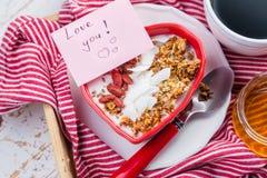 Desayuno del día del ` s de la tarjeta del día de San Valentín - granola con el yogur, las bayas del goji y el coco fotos de archivo