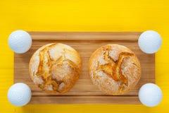 Desayuno del golf - dos panes del trigo y pelotas de golf Fotos de archivo