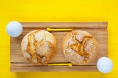 Desayuno del golf - dos panes del trigo y pelotas de golf Imagen de archivo libre de regalías
