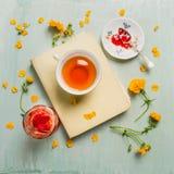 Desayuno del verano con la taza de té, de libro, de atasco y de flores en fondo de madera rústico Fotografía de archivo