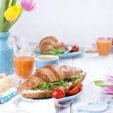 Desayuno delicioso de la primavera en un fondo blanco Ramo de tulipanes frescos Huevos de Pascua coloreados pequeños y grandes Ha Fotos de archivo libres de regalías