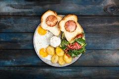Desayuno delicioso grande con los huevos fritos, las patatas fritas, la ensalada fresca, el jamón del pollo en el pan y la salsa  foto de archivo libre de regalías