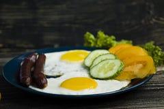 Desayuno delicioso hecho en casa con el lado soleado encima del huevo frito, salchicha, tomates en la visi?n superior imagen de archivo