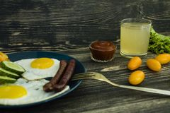 Desayuno delicioso hecho en casa con el lado soleado encima del huevo frito, salchicha, tomates en la visi?n superior foto de archivo