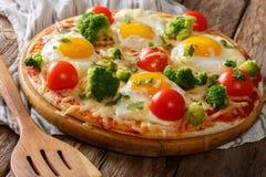 Desayuno delicioso: pizza con los huevos, el bróculi, los tomates y ella imágenes de archivo libres de regalías