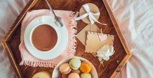 Desayuno en cama con la tarjeta en blanco vacía Taza de café, de jugo, de macarrones, de flor y de giftbox en la bandeja de mader fotografía de archivo