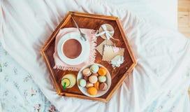 Desayuno en cama con la tarjeta en blanco vacía Taza de café, de jugo, de macarrones, de flor y de giftbox en la bandeja de mader foto de archivo libre de regalías