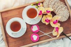Desayuno en cama en día de tarjetas del día de San Valentín Taza de caramelos del té y del dulce Concepto del amor o del día de f Imágenes de archivo libres de regalías
