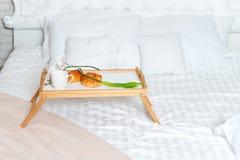 Desayuno en cama, una bandeja de café, cruasanes y flores honeymoon Cama gigante en el apartamento del desván Madrugada en imagen de archivo libre de regalías