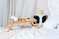 Desayuno en cama, una bandeja de café, cruasanes y flores honeymoon Cama gigante en el apartamento del desván Madrugada en fotos de archivo libres de regalías