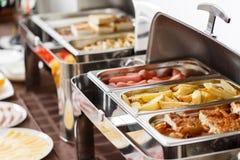 Desayuno en el hotel patatas y huevos revueltos fritos y otros platos calientes Imagenes de archivo