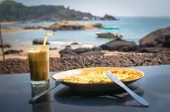 Desayuno en el océano Cóctel en huevos revueltos de cristal y en una placa en el fondo de la playa Imágenes de archivo libres de regalías