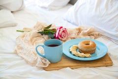 Desayuno en el té de los bollos del hotel y un ramo de flores en cama foto de archivo