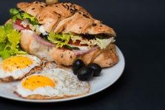 Desayuno en la placa blanca con Fried Eggs y el cruasán con las verduras frescas sobre fondo negro Foto de archivo libre de regalías