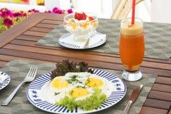 Desayuno en la tabla de madera: lado soleado encima de los huevos y del chee poner crema Imagen de archivo