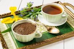 Desayuno en una bandeja: una magdalena del chocolate y una taza de té imagen de archivo