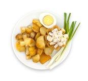 Desayuno en una placa: egg, las patatas fritas, aisladas en blanco Fotografía de archivo