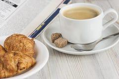 Desayuno francés con los cruasanes, el café y el periódico Imagen de archivo libre de regalías