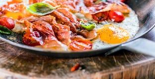 Desayuno heathy de las cacerolas del hierro y de los huevos del tocino foto de archivo