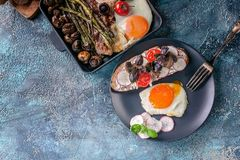 Desayuno hecho en casa delicioso Fried Eggs, bocadillo, queso, verduras, setas, pan e hierbas Visi?n superior fotos de archivo