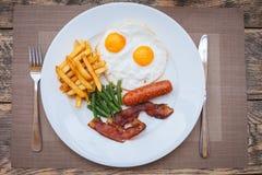 Desayuno inglés con los huevos fritos, el tocino, las salchichas, las habas verdes y las patatas fritas fotos de archivo