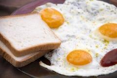 Desayuno inglés, huevos fritos con la tostada en una tabla texturizada vieja fotos de archivo libres de regalías