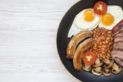 Desayuno inglés lleno en cocinar la cacerola con las salchichas, las setas, los huevos fritos, las habas, el tomate y el tocino e fotos de archivo libres de regalías