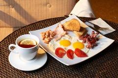 Desayuno inglés tradicional con las habas, los huevos, las verduras, el tocino y la tostada Fotografía de archivo