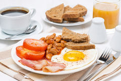 Desayuno inglés tradicional con los huevos fritos, el tocino y las habas Fotografía de archivo libre de regalías