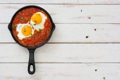 Desayuno mexicano: Rancheros de Huevos en sartén del hierro en la opinión de sobremesa de madera blanca Imagen de archivo