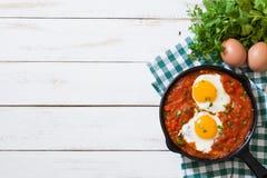 Desayuno mexicano: Rancheros de Huevos en sartén del hierro en la opinión de sobremesa de madera blanca Fotos de archivo