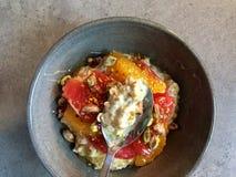 Desayuno: Muesli con el pomelo, segmentos anaranjados, pistachos, polen del kéfir de la abeja Imagen de archivo libre de regalías