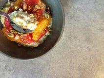 Desayuno: Muesli con el pomelo, segmentos anaranjados, pistachos, polen del kéfir de la abeja Fotos de archivo libres de regalías