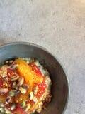 Desayuno: Muesli con el pomelo, segmentos anaranjados, pistachos, polen del kéfir de la abeja Foto de archivo libre de regalías