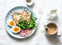 Desayuno o bocado delicioso - salchicha del salami, huevo hervido, arugula, pan asado a la parrilla y café en un fondo ligero fotos de archivo libres de regalías