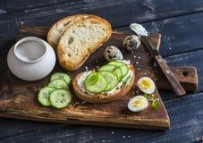 Desayuno o bocado delicioso sano - bocadillo abierto con el queso de cabra y pepino y huevos de codornices hervidos Imagen de archivo libre de regalías