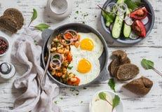 Desayuno o bocado delicioso - un huevo frito, habas en salsa de tomate con las cebollas y zanahorias, pepinos frescos y tomates,  Fotografía de archivo libre de regalías