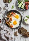 Desayuno o bocado delicioso - un huevo frito, habas en salsa de tomate con las cebollas y zanahorias, pepinos frescos y tomates,  Imagen de archivo libre de regalías