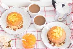 Desayuno para 2 Bandeja con 2 placas del vintage de crepes con el atasco anaranjado y nueces y 2 tazas del café con leche Visión  Foto de archivo libre de regalías