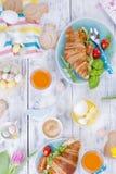 Desayuno para dos Cruasanes con la ensalada y el café express Jugo y dulces frescos Tulipanes de la primavera Decoración de Pascu Fotos de archivo libres de regalías