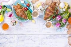 Desayuno para dos Cruasanes con la ensalada y el café express Jugo y dulces frescos Tulipanes de la primavera Decoración de Pascu Foto de archivo