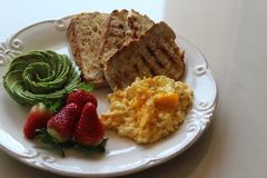 Desayuno perfecto con la tostada, el aguacate, el huevo y las bayas fotografía de archivo libre de regalías