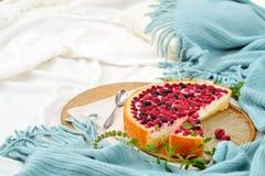 Desayuno plano de la endecha en cama con el pastel de queso de la frambuesa, té de la menta Foto de archivo
