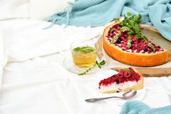 Desayuno plano de la endecha en cama con el pastel de queso de la frambuesa, té de la menta Fotos de archivo