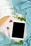 Desayuno plano de la endecha en cama con el pastel de queso de la frambuesa, el té y el cuaderno abierto, tableta de la menta Foto de archivo libre de regalías